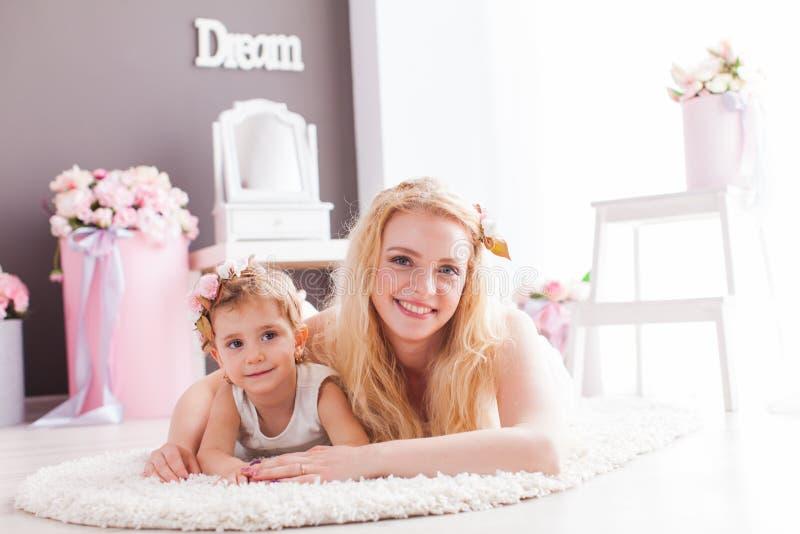 Hija feliz y mamá sonrientes que ponen en un piso en su casa imagen de archivo
