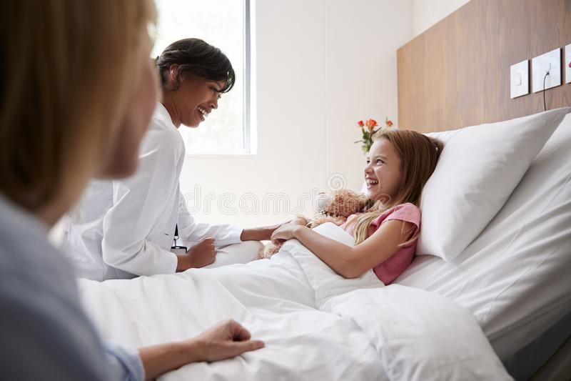 Hija femenina del doctor Visiting Mother And que miente en cama en sala de hospital imagen de archivo libre de regalías