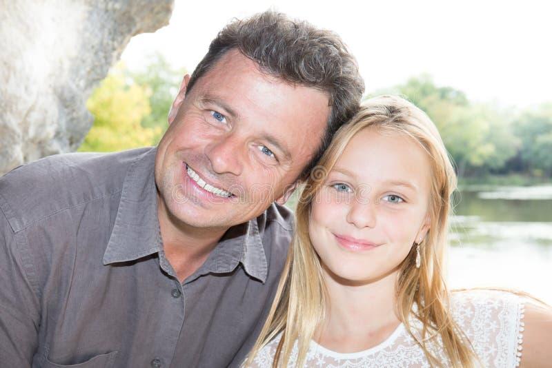 Hija hermosa rubia con amor sonriente del padre alegre en parque imagen de archivo
