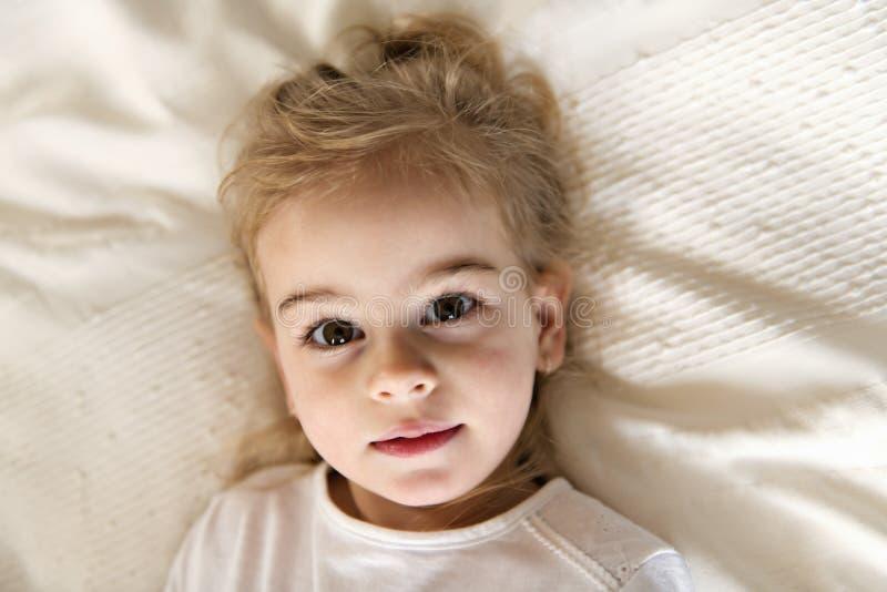 Hija joven dos años que se relajan en cama, sensaciones positivas foto de archivo libre de regalías