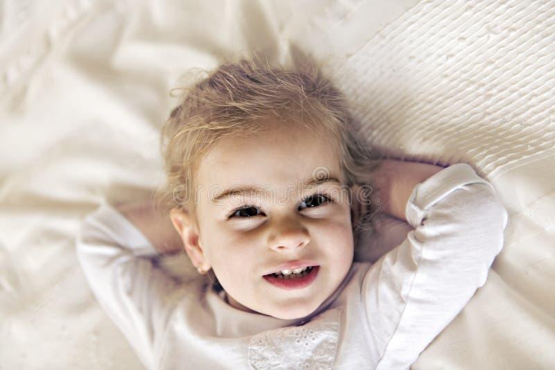 Hija joven dos años que se relajan en cama, sensaciones positivas imagen de archivo libre de regalías