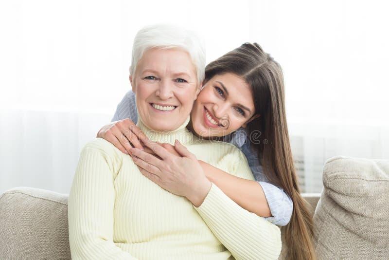 Hija joven que abraza a su madre con amor imagen de archivo libre de regalías