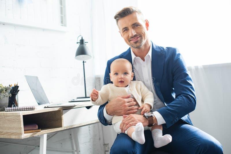 hija pequeña feliz y sonrisa de la tenencia del hombre de negocios imagenes de archivo