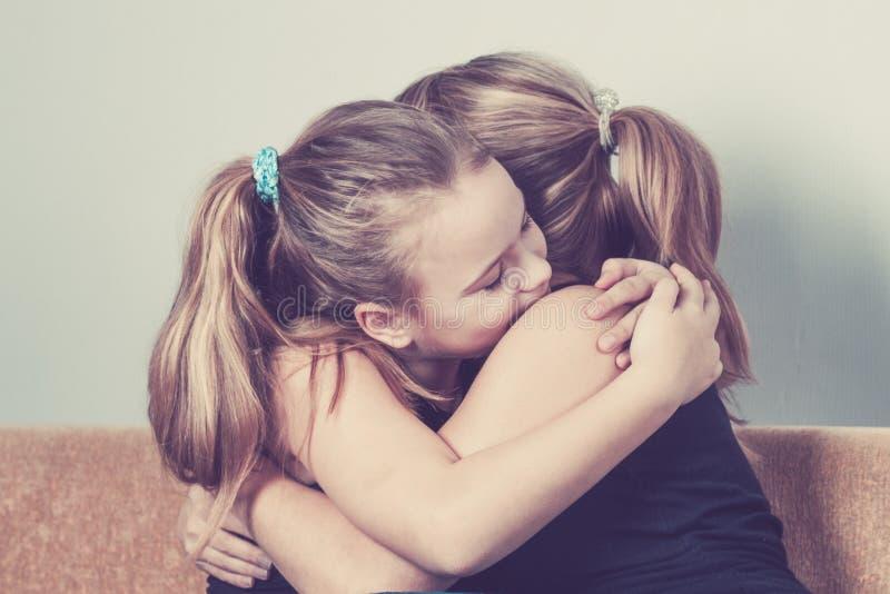 Hija que abraza a su madre en casa El concepto de familia de los pares está en dolor imagen de archivo