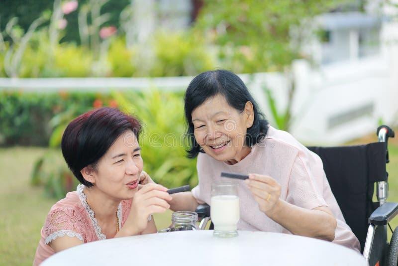 Hija que cuida para la mujer asiática mayor, escogiendo un chocolate imagenes de archivo
