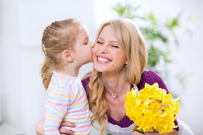 Hija que da las flores y beso al mohter feliz sonriente imágenes de archivo libres de regalías