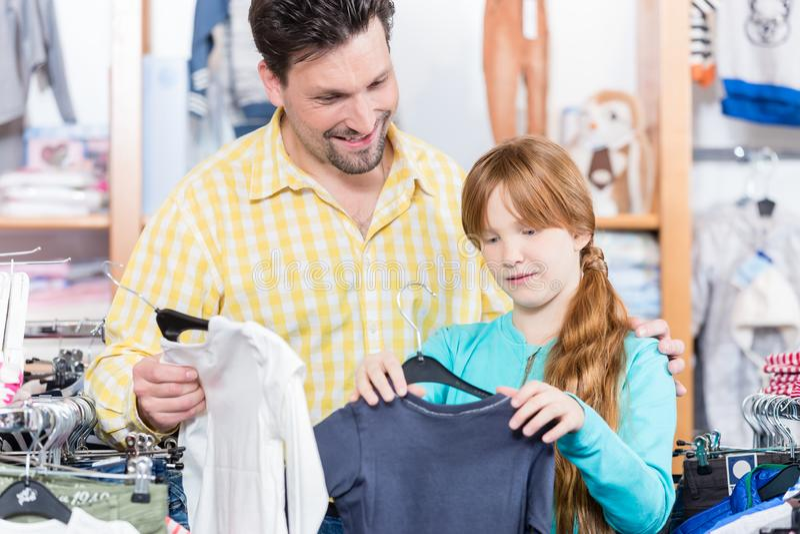 Hija que elige la camiseta en la tienda al por menor fotos de archivo