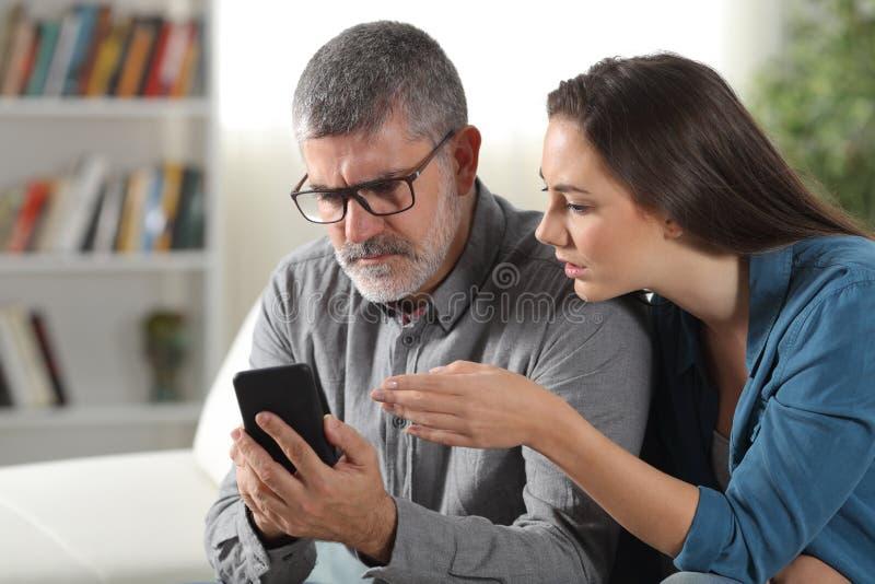 Hija que enseña a cómo utilizar un teléfono a su padre foto de archivo libre de regalías
