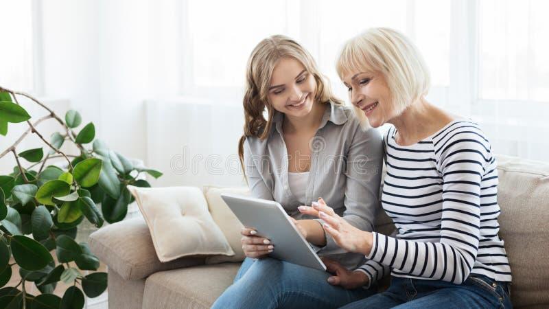 Hija que enseña a la madre mayor a utilizar la tableta fotos de archivo