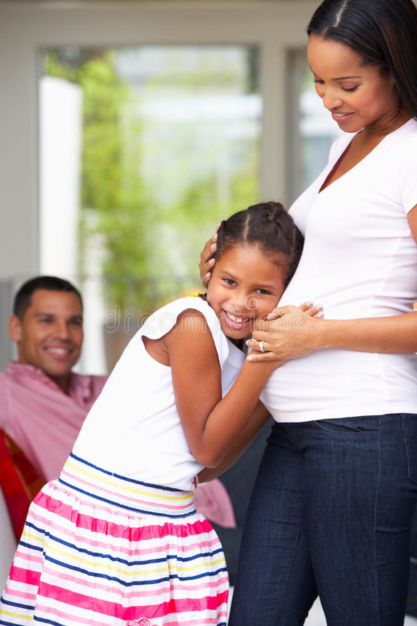 Hija que escucha el estómago de la madre embarazada imagen de archivo libre de regalías