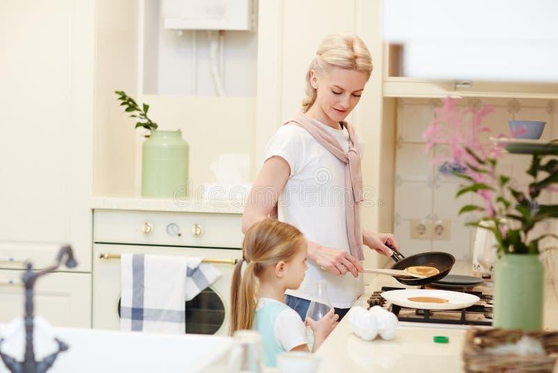 Hija que espera cuando la madre cocina las crepes fotos de archivo libres de regalías