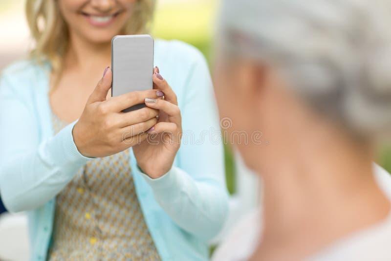Hija que fotograf?a a la madre mayor por smartphone fotos de archivo libres de regalías