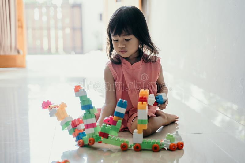Hija que juega con el ladrillo plástico en casa imagen de archivo