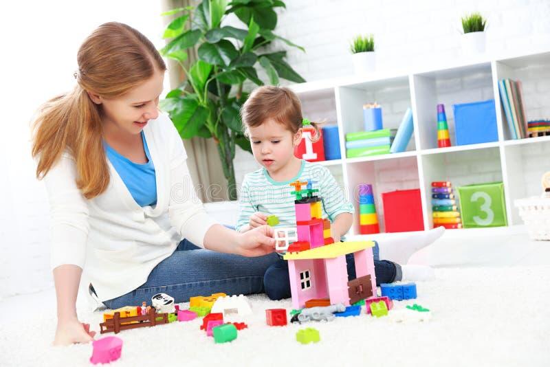 Hija que juega, estructura de la madre y del niño del constructor foto de archivo libre de regalías