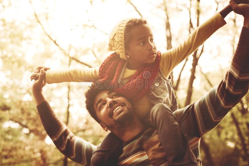 Hija que lleva del padre afroamericano en hombros foto de archivo