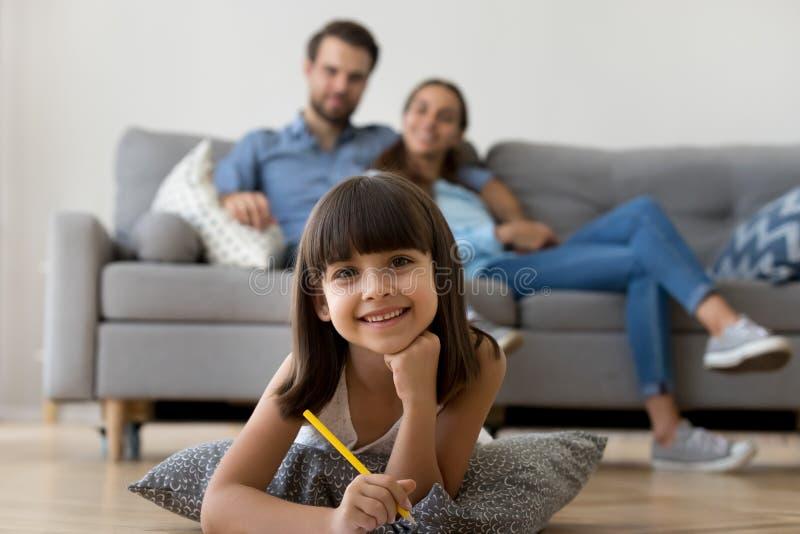 Hija que mira la cámara que miente en el lápiz de la tenencia del dibujo del piso imágenes de archivo libres de regalías