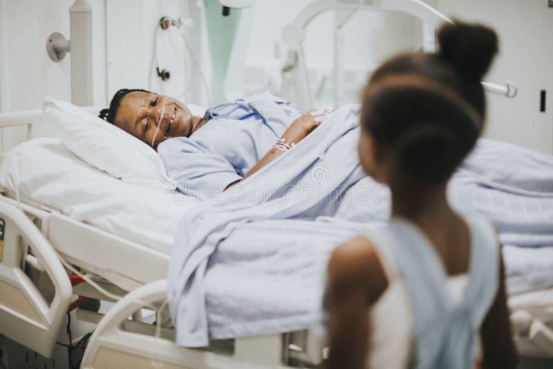 Hija que mira su sueño de la abuela en el hospital fotos de archivo