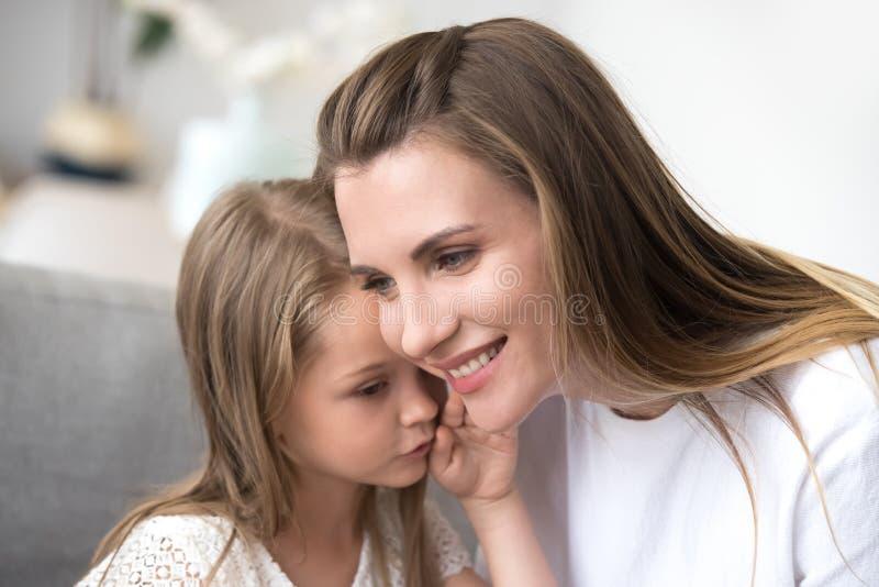 Hija que susurra al oído de las mamáes un secreto imagen de archivo libre de regalías