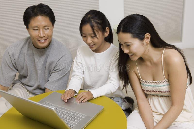 Hija que usa el ordenador portátil con la madre y el padre en sala de estar fotos de archivo