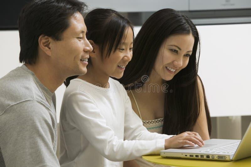 Hija que usa el ordenador portátil con la madre y el padre en sala de estar fotos de archivo libres de regalías