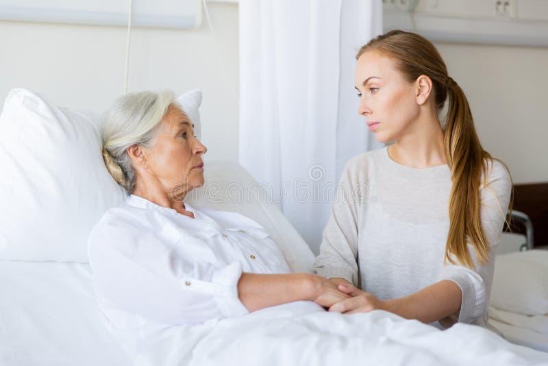 Hija que visita a su madre mayor en el hospital fotos de archivo libres de regalías