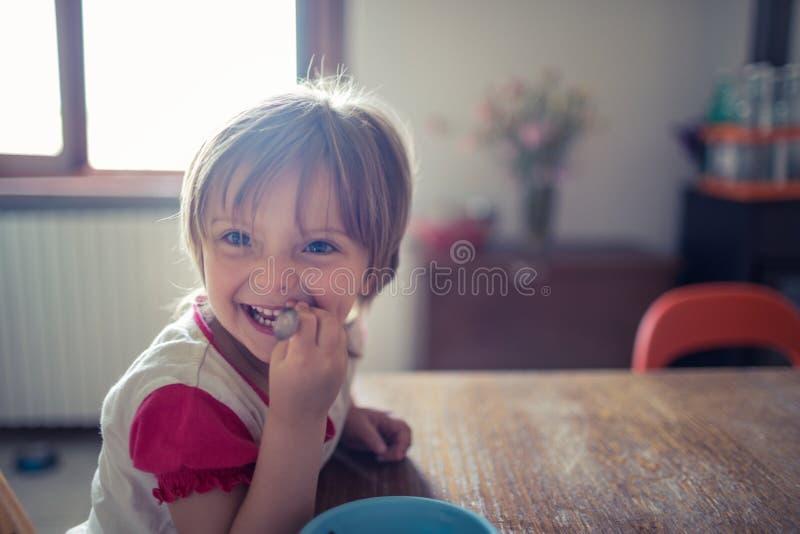 Hija rubia feliz de la muchacha con los ojos azules que sonríe mientras que juega en el piso de madera de la sala de estar Famili imagenes de archivo