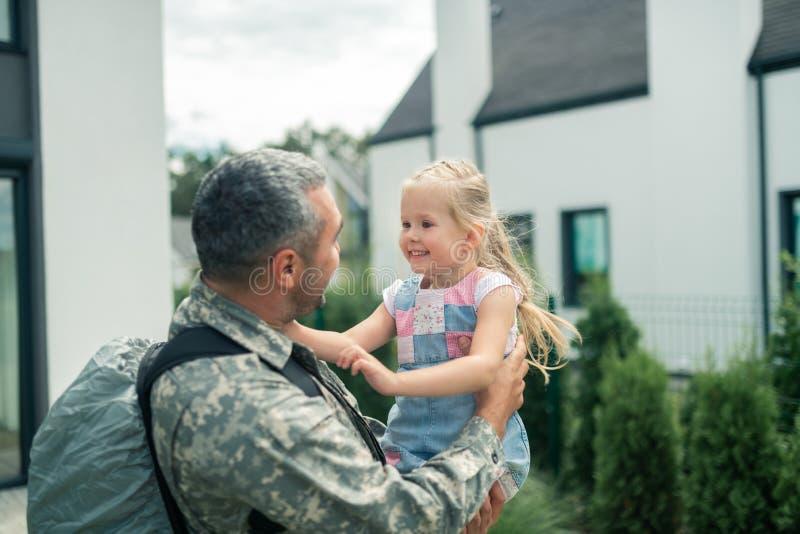 Hija rubio-cabelluda alegre que sonríe mientras que mira al papá foto de archivo