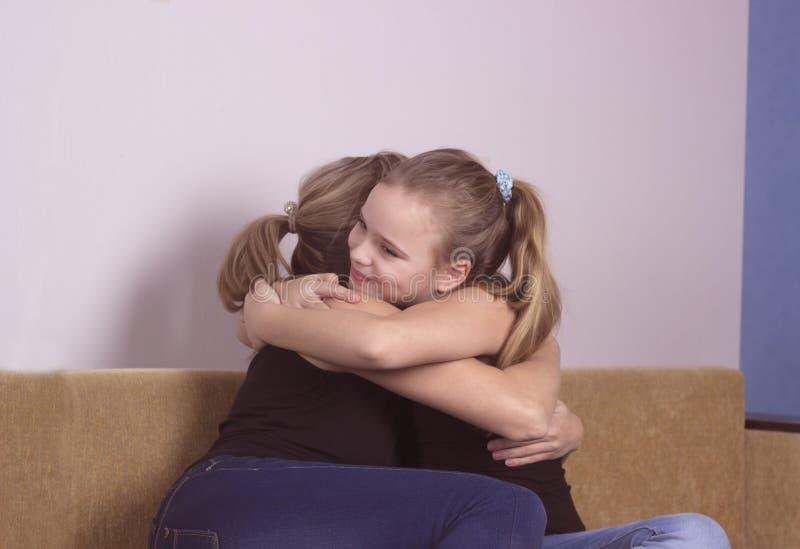 Hija sonriente que abraza a su madre en casa El concepto de familia de los pares está en dolor fotos de archivo libres de regalías