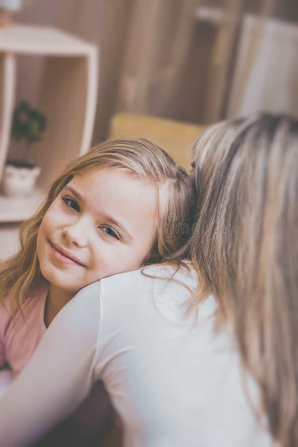 Hija sonriente que abraza a su madre en casa El concepto de familia de los pares está en dolor imagen de archivo