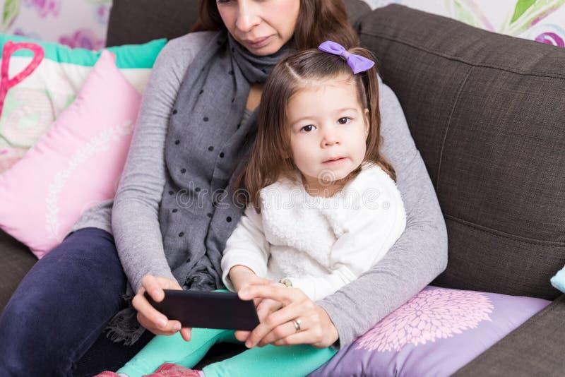 Hija y madre con Smartphone en casa foto de archivo