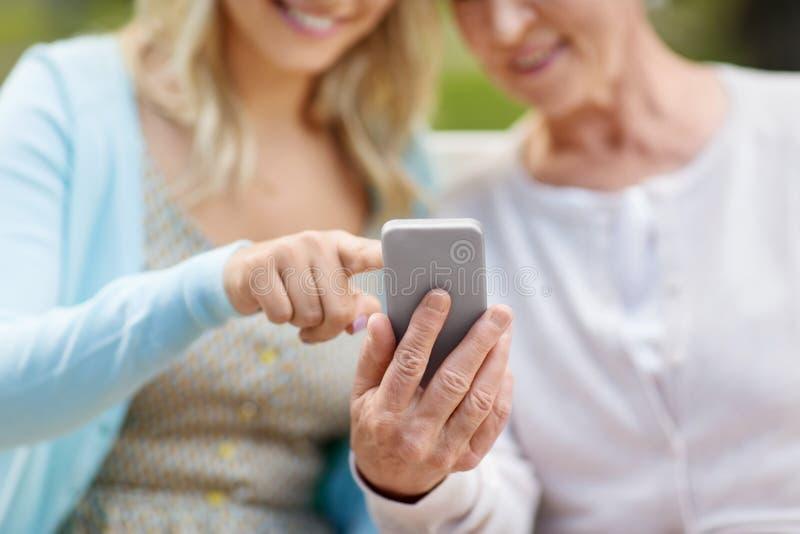 Hija y madre mayor con smartphone en el parque imagen de archivo