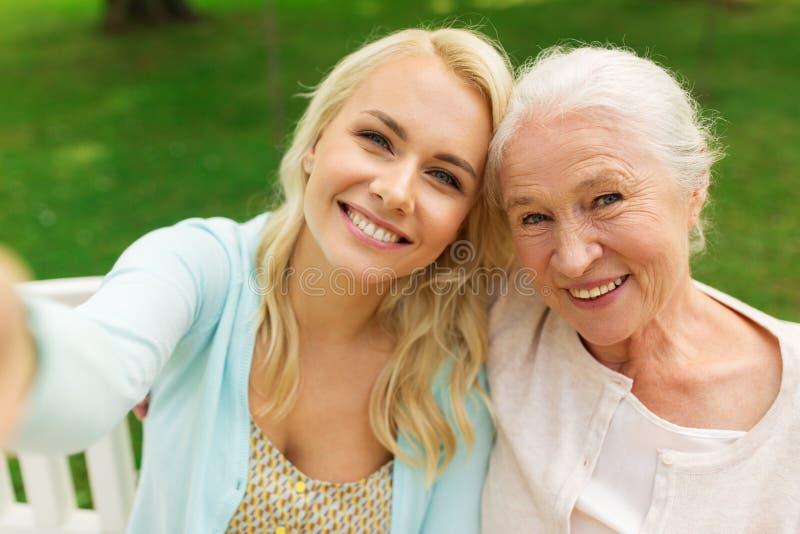 Hija y madre mayor que toman el selfie en el parque fotografía de archivo