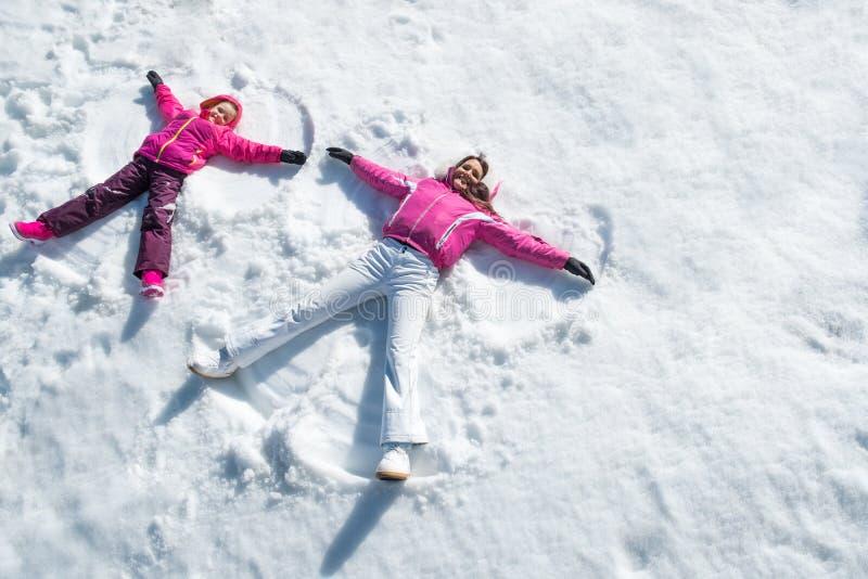Hija y madre que ponen en nieve fotos de archivo