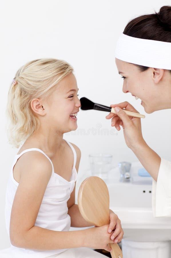 Hija y madre que ponen maquillaje foto de archivo