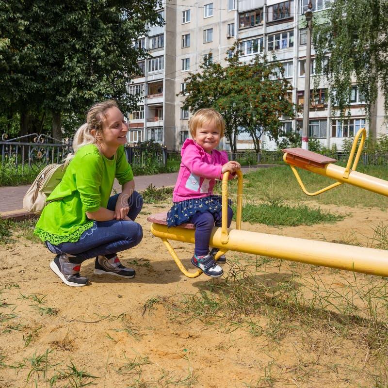 Hija y madre satisfechas en el oscilación en el patio imagenes de archivo