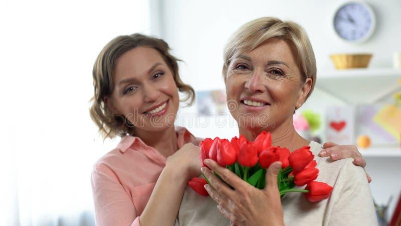 Hija y mamá bonitas con los tulipanes que sonríen en la cámara, celebración del día de madres imagen de archivo