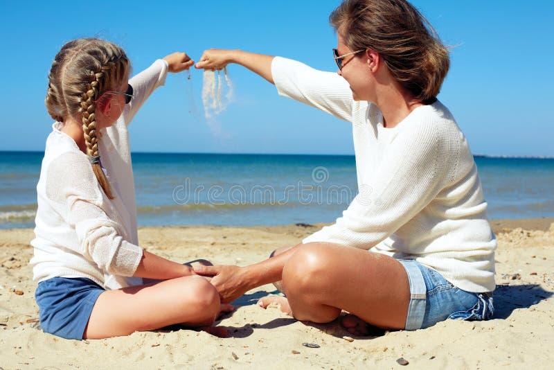 Hija y su mamá que juegan con la arena en la playa imagen de archivo libre de regalías