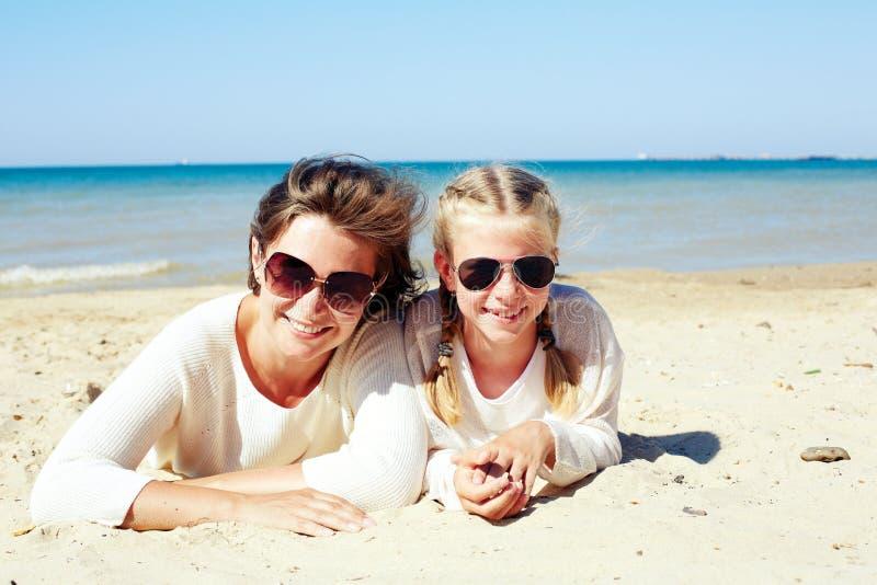 Hija y su mamá que juegan con la arena en la playa imagenes de archivo