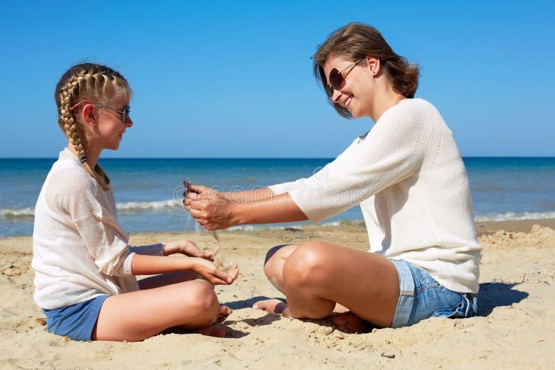 Hija y su mam? que juegan con la arena en la playa imagen de archivo