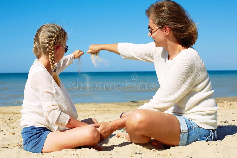 Hija y su mam? que juegan con la arena en la playa Junto imagenes de archivo