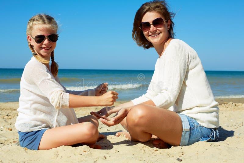 Hija y su mam? que juegan con la arena en la playa fotografía de archivo libre de regalías