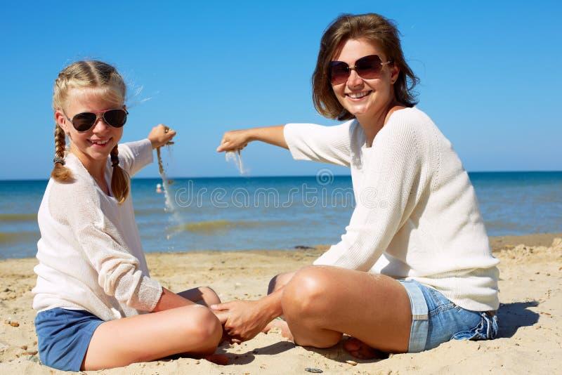 Hija y su mam? que juegan con la arena en la playa imagen de archivo libre de regalías