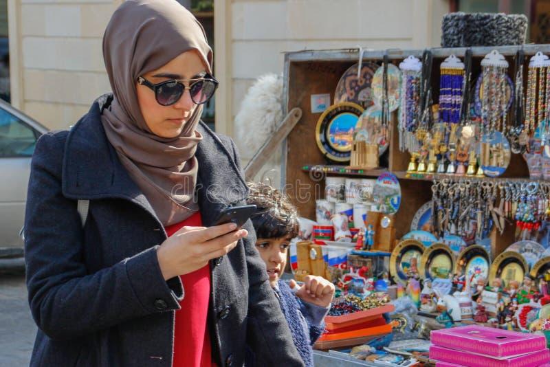 hijab和玻璃步行的一名年轻Aresbaidan妇女沿老镇的街道有传统阿塞拜疆纪念品的 库存图片