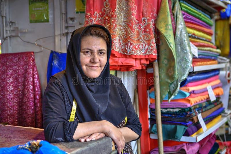 hijab的一名成熟伊朗妇女在义卖市场卖纺织品 库存照片