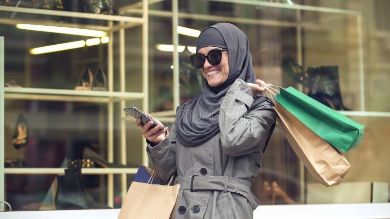 hijab的可爱的微笑的女性购物和聊天在有朋友的电话的 免版税库存图片