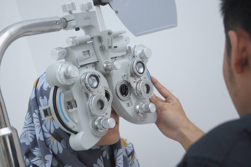 hijab的女孩审查用设备在optomitrists办公室分析眼睛包括phoropter 免版税库存照片