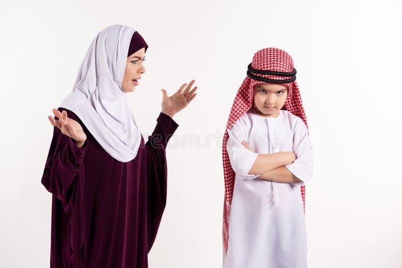 hijab的阿拉伯妇女责骂keffiyeh的男孩 库存照片
