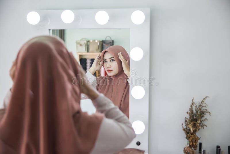 Hijab женщины нося в зеркале стоковое фото rf