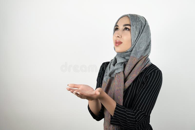 Hijab тюрбана молодой красивой надеющийся мусульманской женщины нося, головной платок держа ее руки совместно изолировало белое стоковая фотография rf