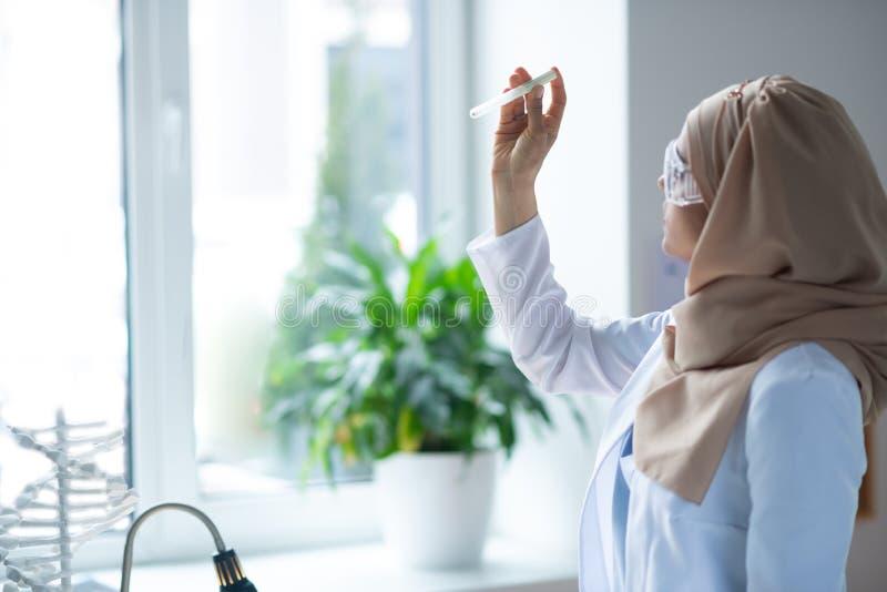 Hijab химика нося держа положение пробирки около окна стоковая фотография rf